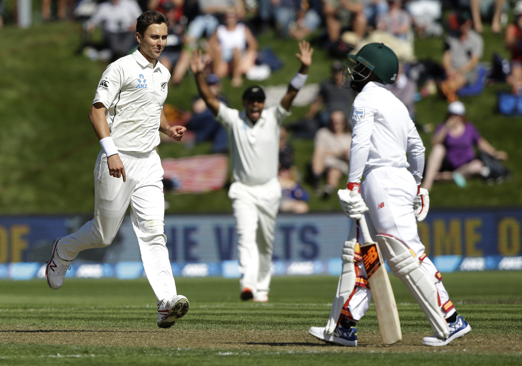 New Zealand's Trent Boult, left, reacts after dismissing South Africa's Temba Bavuma, right during the first cricket test at University...