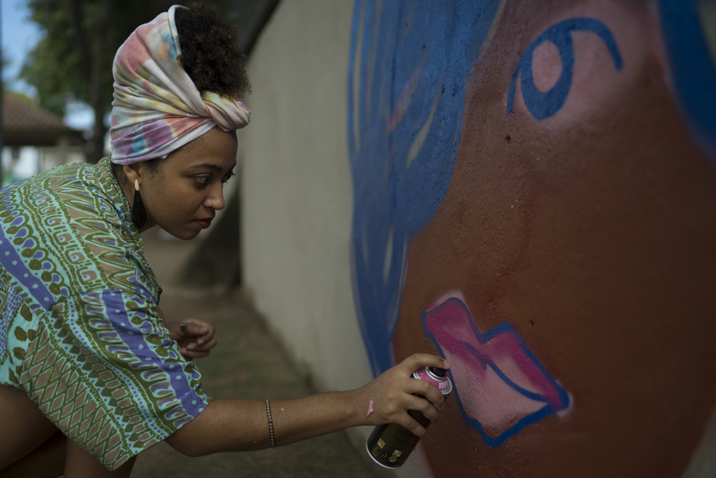 "Graffiti artist Maiara Viana Rodrigues paints a mural at her home neighborhood in Rio de Janeiro, Brazil, March 7, 2017. ""We use graffi..."