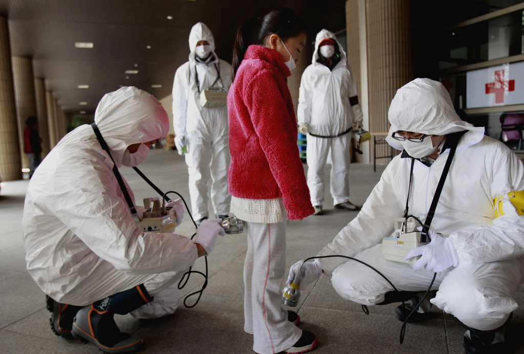 FILE - In this March 24, 2011 file photo, a young evacuee is screened at a shelter for leaked radiation from the tsunami-ravaged Fukush...