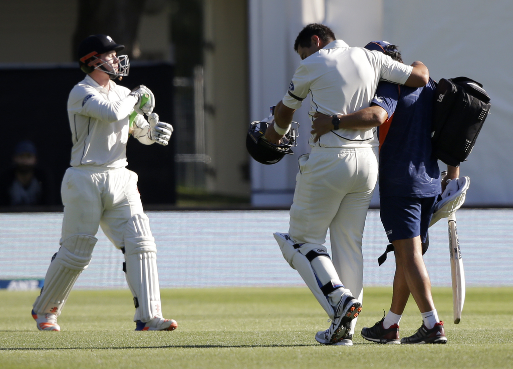 New Zealand's Ross Taylor, centre, is assisted from the field after injuring his leg as teammate Henry Nicholls comes out to bat during...