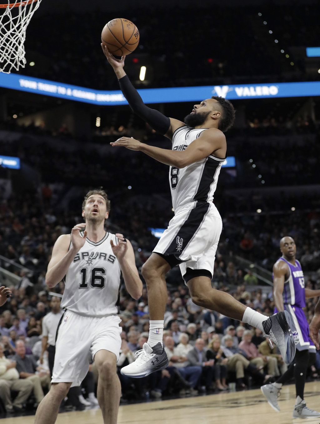 San Antonio Spurs guard Patty Mills (8) drives to the basket past teammate Pau Gasol (16) during the second half of the team's NBA bask...