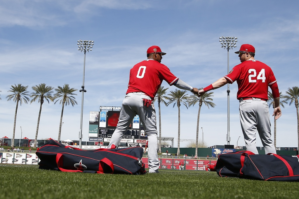 Los Angeles Angels' Yunel Escobar (0) and C.J. Cron (24) fist bump as the warm up prior to a spring training baseball game against the ...