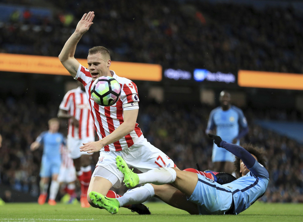 Stoke City's Ryan Shawcross, left, and Manchester City's Leroy Sane battle in action during the English Premier League soccer match at ...