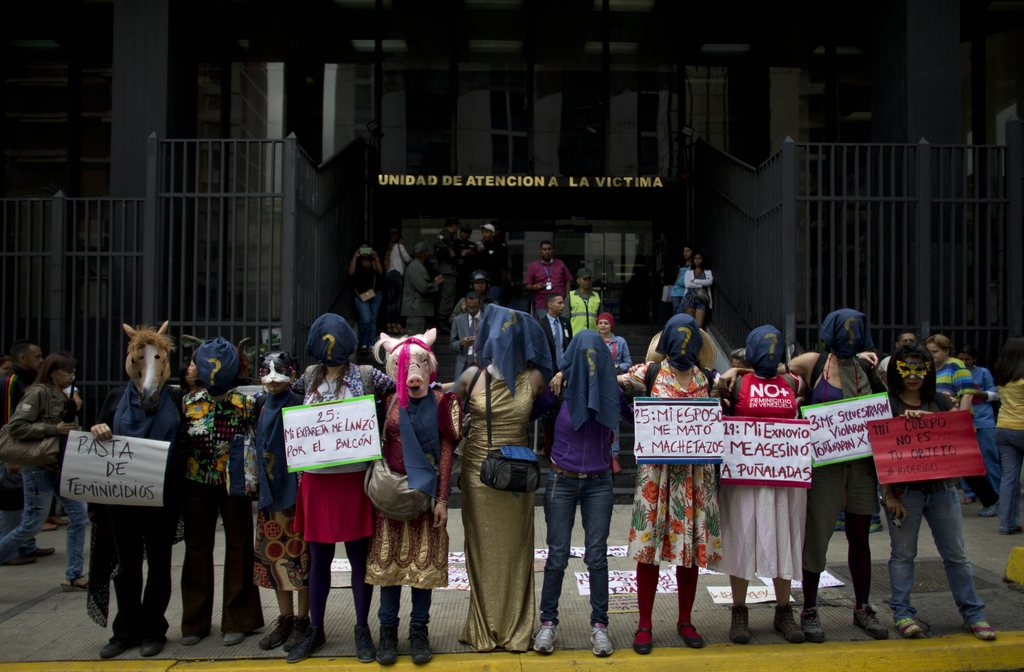 A group of women wearing masks a protest against violence against women outside of the General Prosecutor's Office in Caracas, Venezuel...