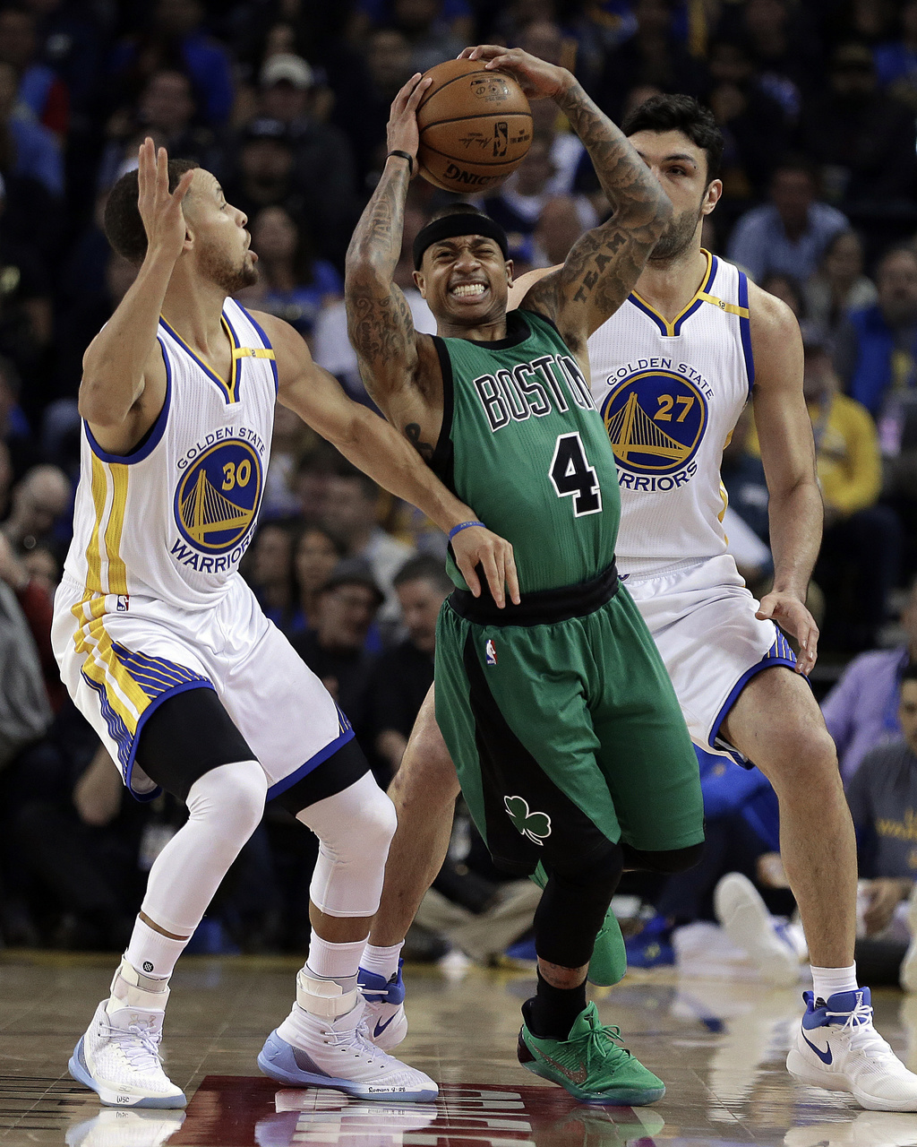 Boston Celtics' Isaiah Thomas (4) looks to pass away from Golden State Warriors'Stephen Curry, left, and Zaza Pachulia (27) during the ...