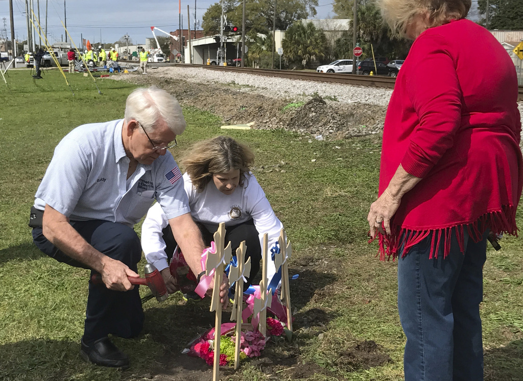 Serena Gilich watches as Buddy Hammett, and Laurie Kuluz place crosses and flowers at the north side of the railroad tracks on Wednesda...