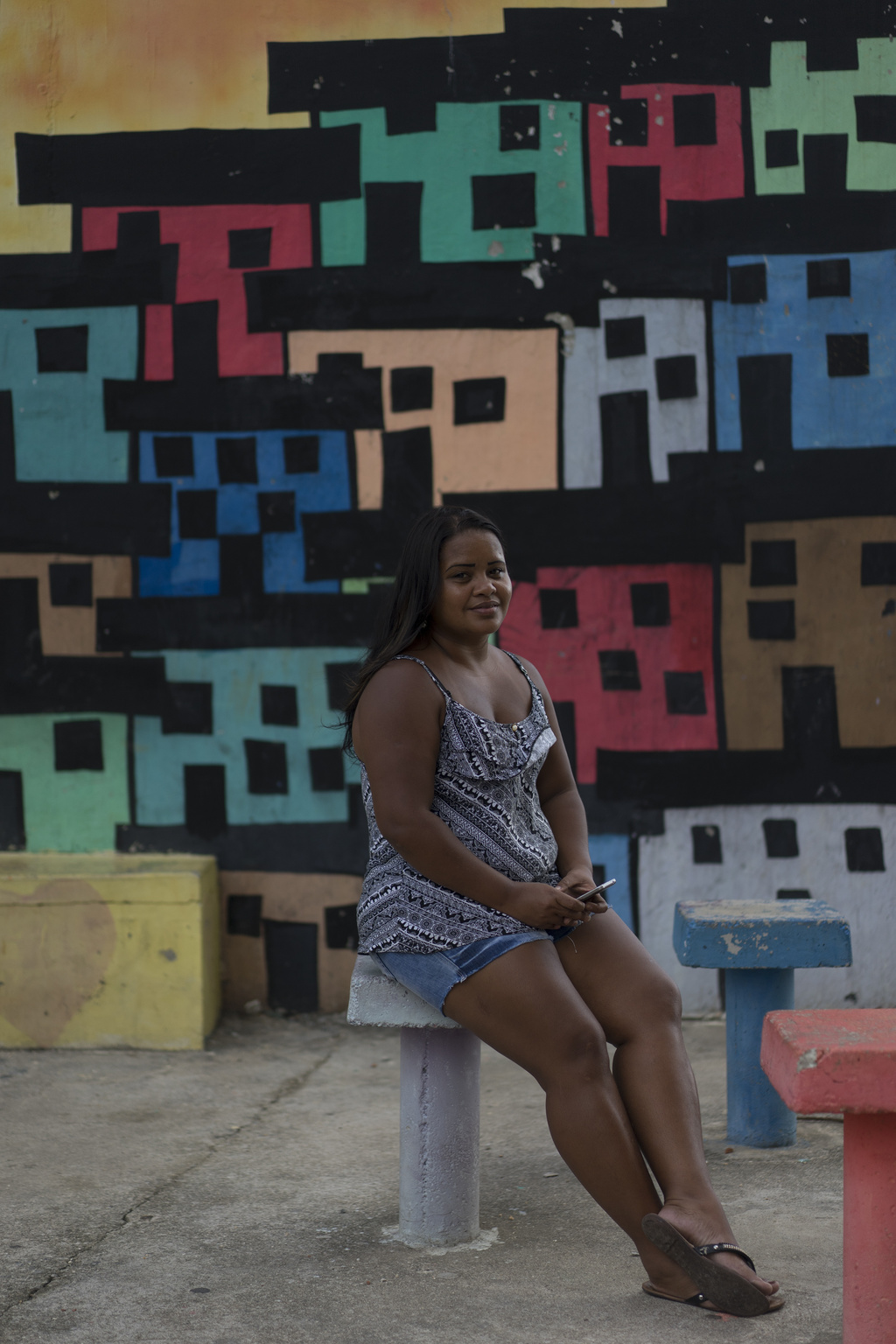 In this March 7, 2017, photo, artist Mariluce Maria de Souza poses for a picture in front of one of her murals at the Alemao slum in Ri...