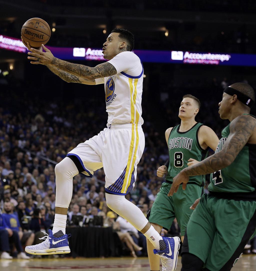 Golden State Warriors' Matt Barnes lays up a shot past Boston Celtics' Jonas Jerebko (8) and Isaiah Thomas, right, during the first hal...