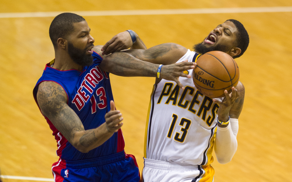 Indiana Pacers forward Paul George (13) makes contact with Detroit Pistons forward Marcus Morris (13) as he drives the ball to the bask...