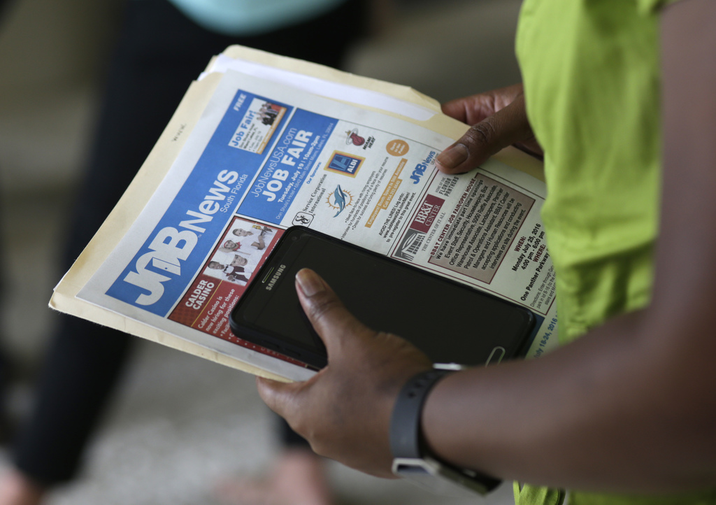 FILE - In this Tuesday, July 19, 2016, file photo, a job applicant attends a job fair in Miami Lakes, Fla.  The Labor Department says a...