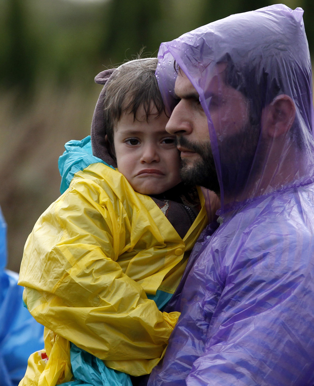 FILE - In this Sept. 24, 2015 file photo a man carries a child to board a train at a station near the village of Zakany, Hungary. UNICE...