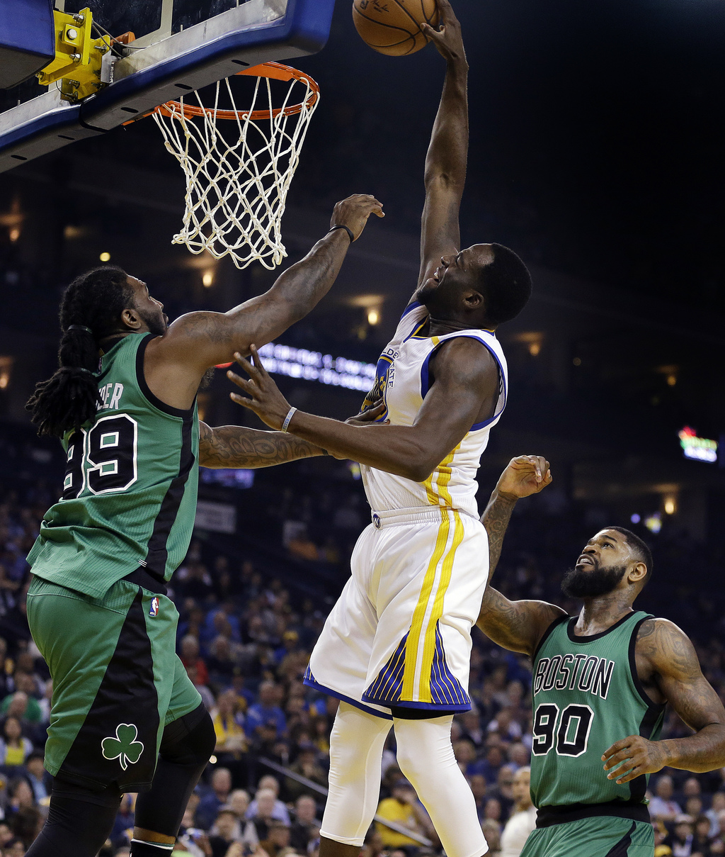 Golden State Warriors' Draymond Green, center, shoots over Boston Celtics' Jae Crowder, left, and Amir Johnson, right, during the first...