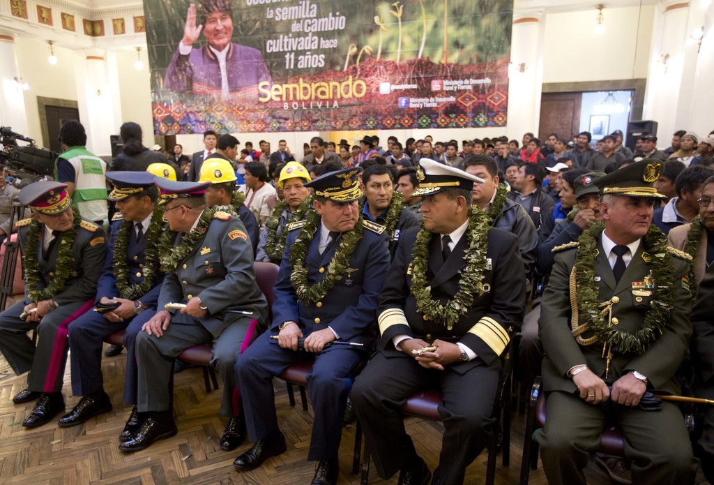 Military leaders and police chiefs wear garlands made from coca leaves as they wait for the start of a signing ceremony for the new coc...