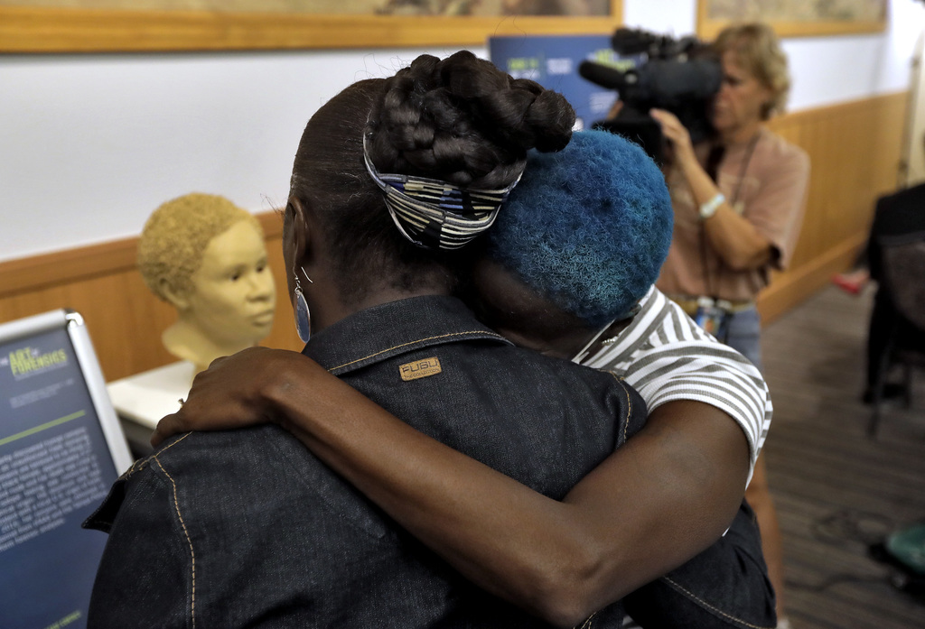 In this Oct. 21, 2016 photo, Sharon Scott, left, and Sheila Williams console each other near a sculpture of an unidentified 1985 female...