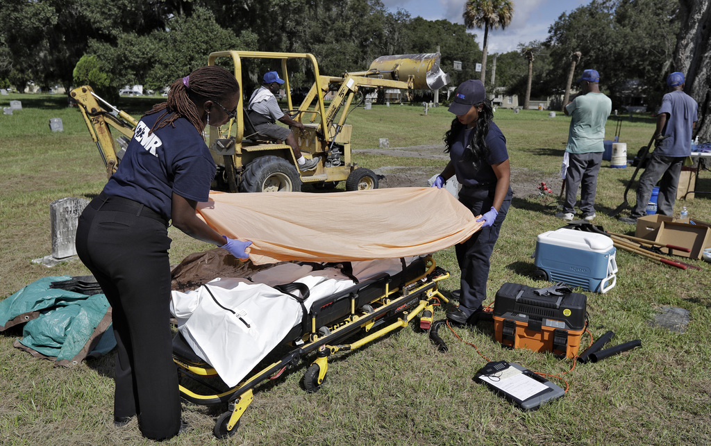 In this Sept. 15, 2016 photo, medical workers prepare to take the remains of an unidentified 1985 female murder victim to the medical e...