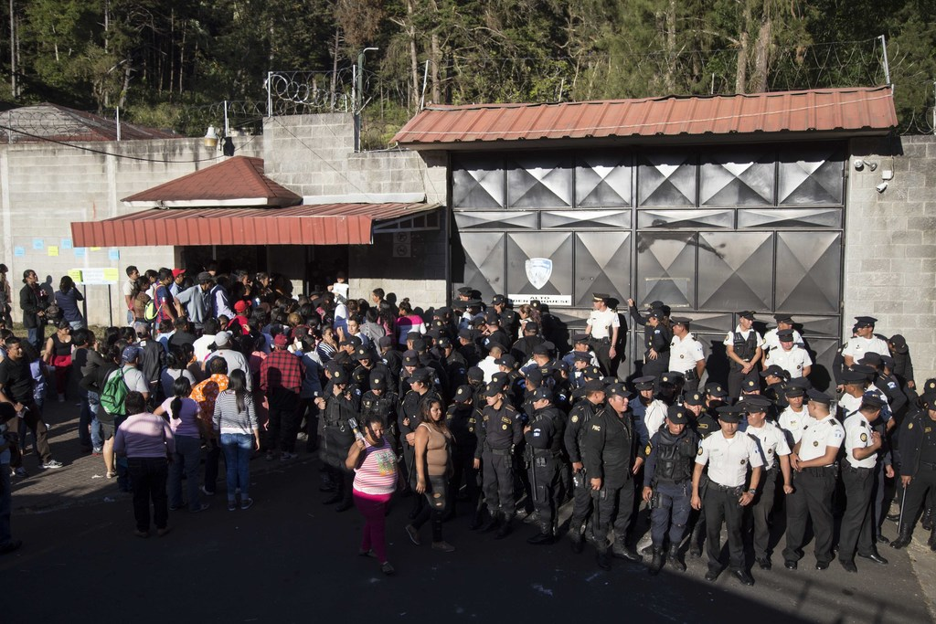 National Police guard the entrance to the children's shelter Virgin of the Assumption Safe Home where people gather in San Jose Pinula,...