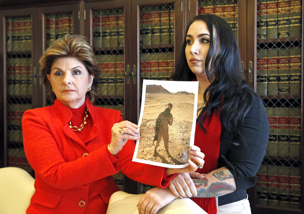 Former Marine Erika Butner, right, and attorney Gloria Allred hold photos of Butner in uniform, as she and another active-duty female M...