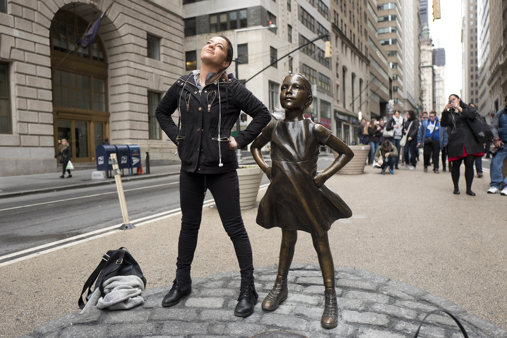 "A woman strikes a pose in front of a statue titled ""Fearless Girl"" on Wednesday, March 8, 2017, in New York. A big investment firm, Sta..."