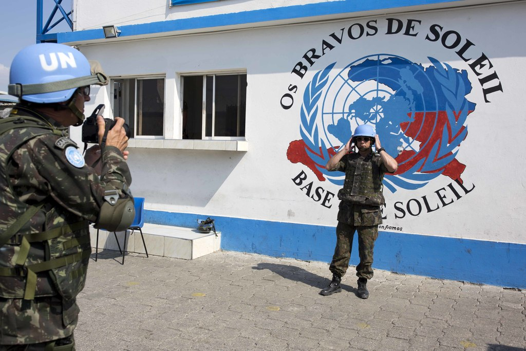 In this Feb. 22, 2017 photo, a U.N. peacekeeper from Brazil poses for a souvenir photo before the start of a patrol in the Cite Soleil ...
