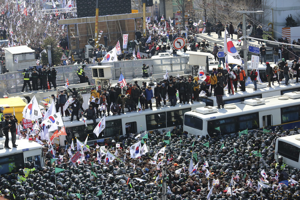 Supporters of South Korean President Park Geun-hye are blocked by police buses as they march toward Constitutional Court after a rally ...
