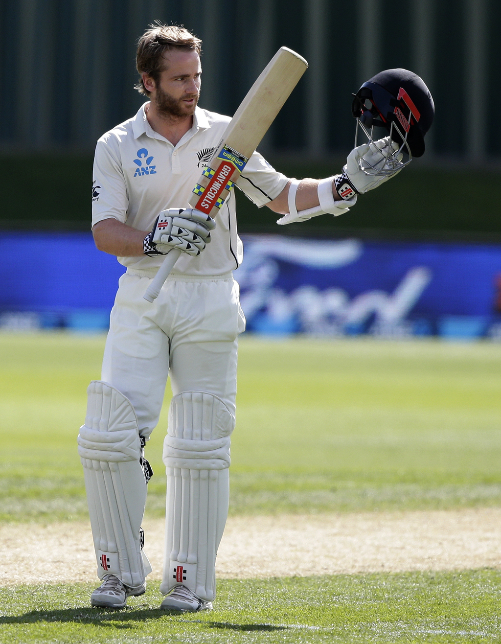 New Zealand's Kane Williamson waves to the crowd after scoring a century against South Africa during the first cricket test at Universi...