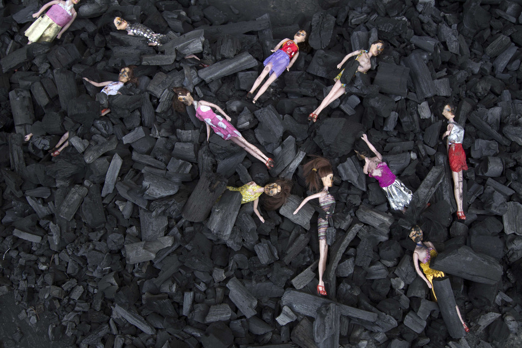 Charred-stained dolls placed on a bed of charcoal is part of artists' installation placed at the front gate of Presidential House, in r...
