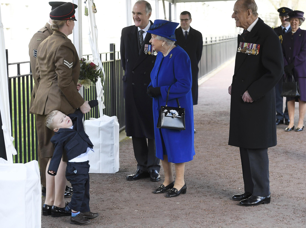 Michelle Lun, left, holds on to her son Alfie, 2-years-old as they meet Britain's Queen Elizabeth II at the unveiling  during the the u...