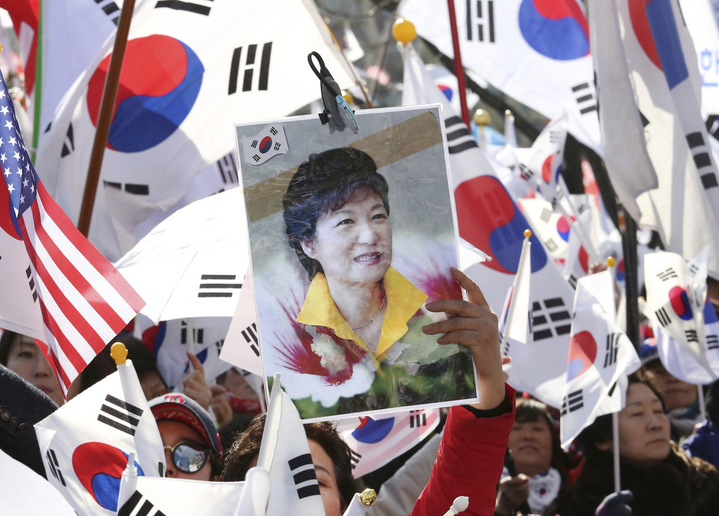 A supporter of South Korean President Park Geun-hye holds up her portrait during a rally opposing her impeachment in Seoul, South Korea...