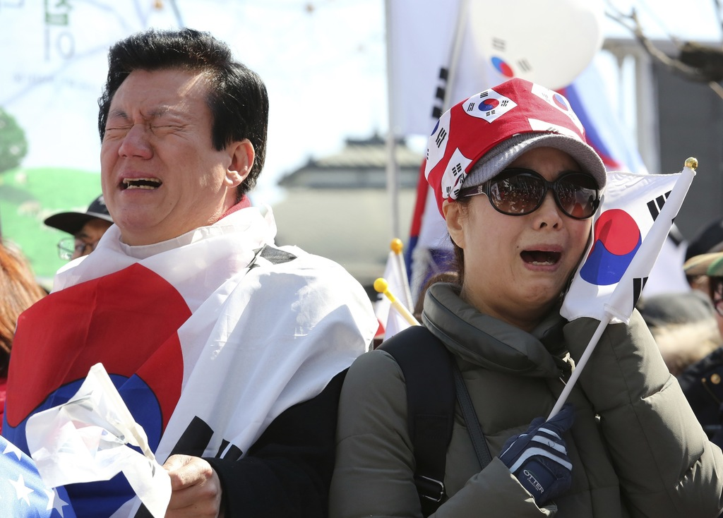 In this Friday, March 10, 2017, photo, supporters of South Korean President Park Geun-hye cry during a rally opposing her impeachment n...