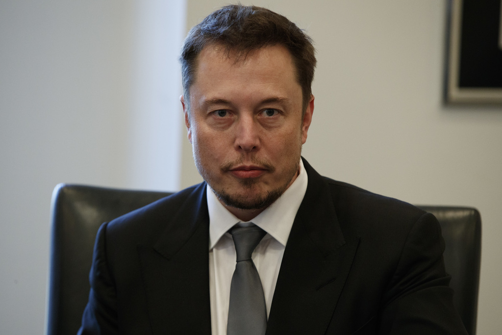 FILE - In this Dec. 14, 2016, file photo, Tesla CEO Elon Musk listens as President-elect Donald Trump speaks during a meeting with tech...