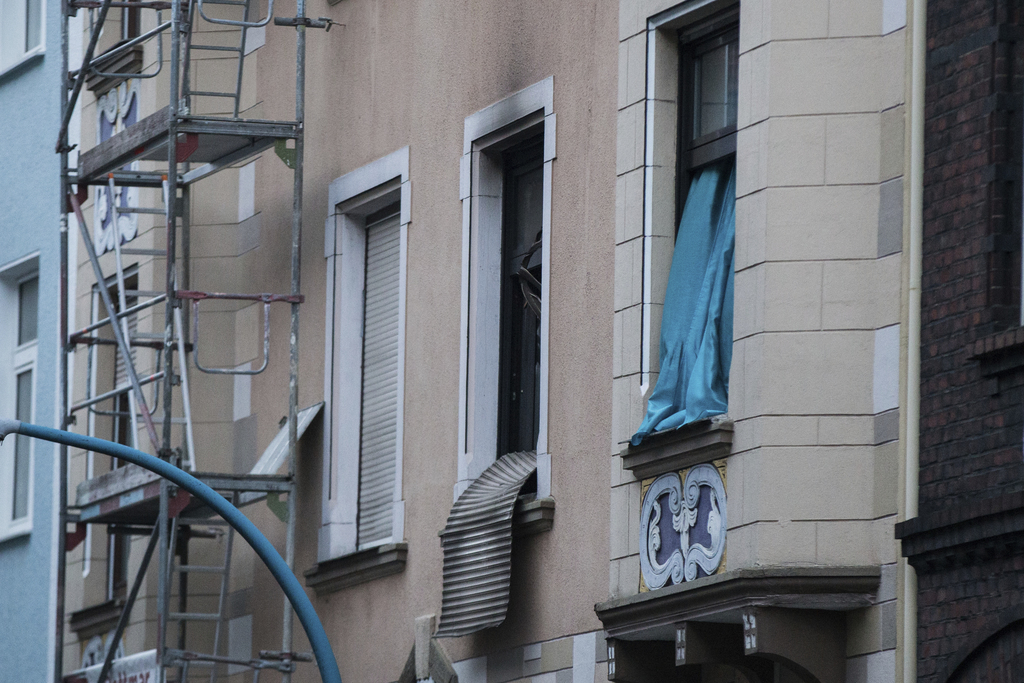 A destroyed roller shutter hangs from a burnt out apartment window in Herne, western Germany, Friday, March 10, 2017. German police say...