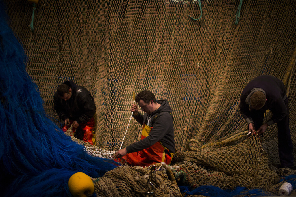 In this Friday, March 3, 2017 photo, fishermen of the Maarten-Jacob ship work fixing their fishing net at the port in The Hague, The Ne...