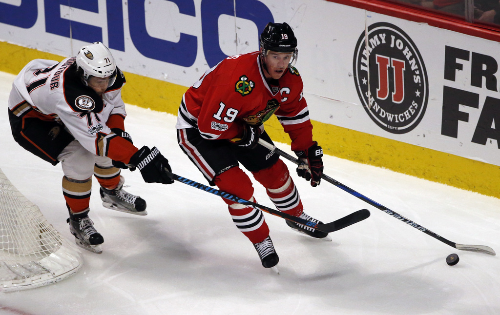 Chicago Blackhawks center Jonathan Toews, right, controls the puck as he looks to pass against Anaheim Ducks defenseman Brandon Montour...