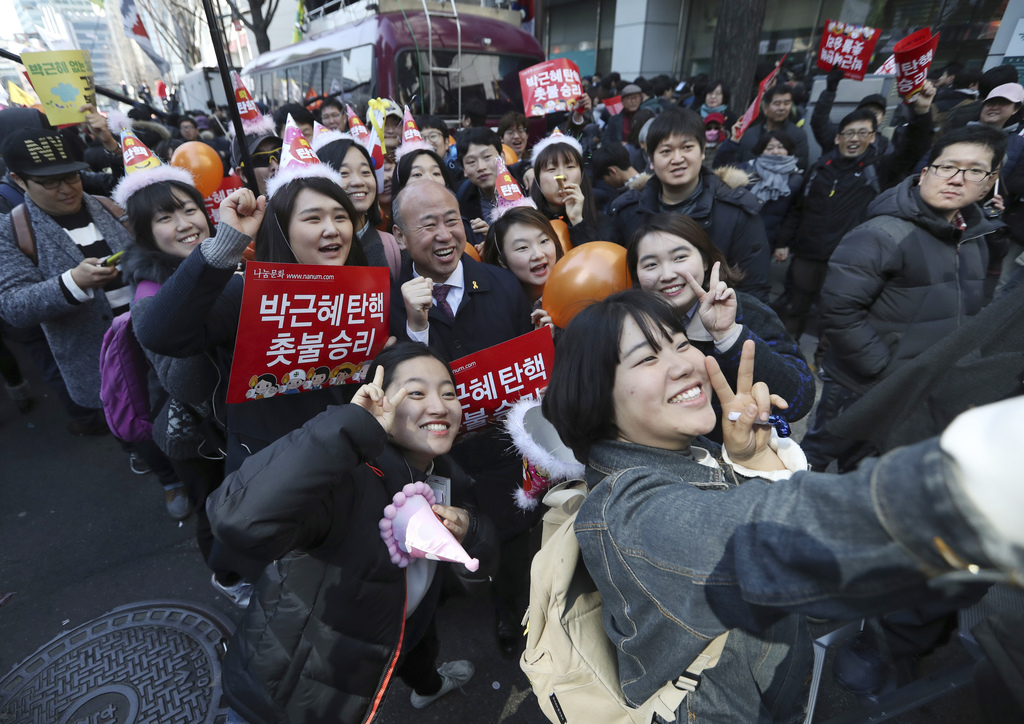 Protesters take a selfie after the Constitutional Court's verdict during a rally calling for impeachment of President Park Geun-hye nea...