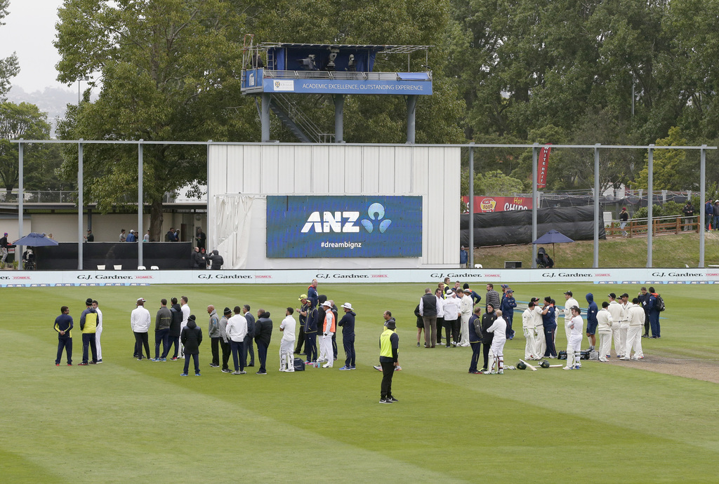 Players and officials wait on the field after the main grandstand and public viewing areas were cleared by security staff during the fi...