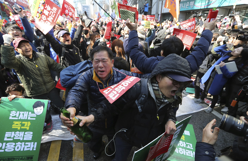 Protesters open a bottle of champagne to celebrate during a rally calling for impeachment of President Park Geun-hye near the Constitut...