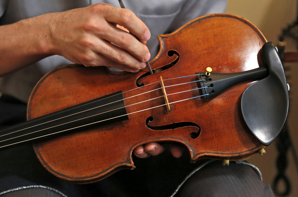 In this Wednesday, March 8, 2017 photo, Tatsuo Imaishi makes an adjustment on the Ames Stradivarius violin in New York. After a meticul...