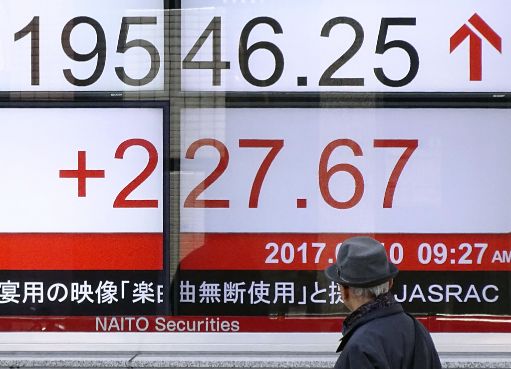 A man looks at an electronic stock board of a securities firm showing Tokyo's Nikkei 225 stock index in Tokyo, Friday, March 10, 2017. ...