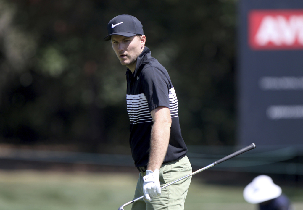 Russell Henley inspects his lie at the seventh hole while playing in the first round of the Valspar Golf Championship at Innisbrook Res...