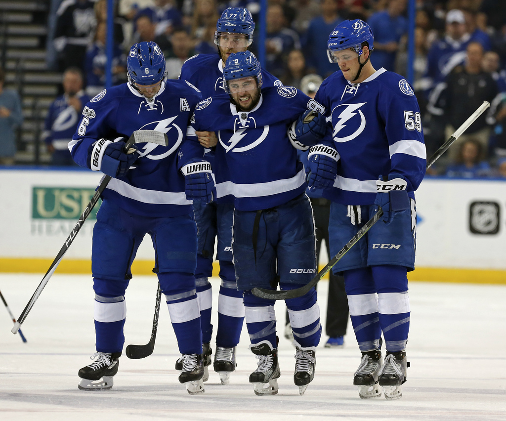 Tampa Bay Lightning's Tyler Johnson, center, is helped off the ice by Anton Stralman, left, of Sweden, and Jake Dotchin as Victor Hedma...