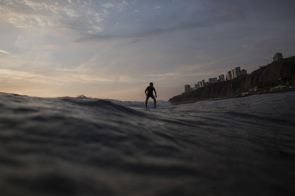 In this Monday, March 6, 2017 photo, a man surfs as the sun sets, at Waikiki beach in Lima, Peru. (AP Photo/Rodrigo Abd)