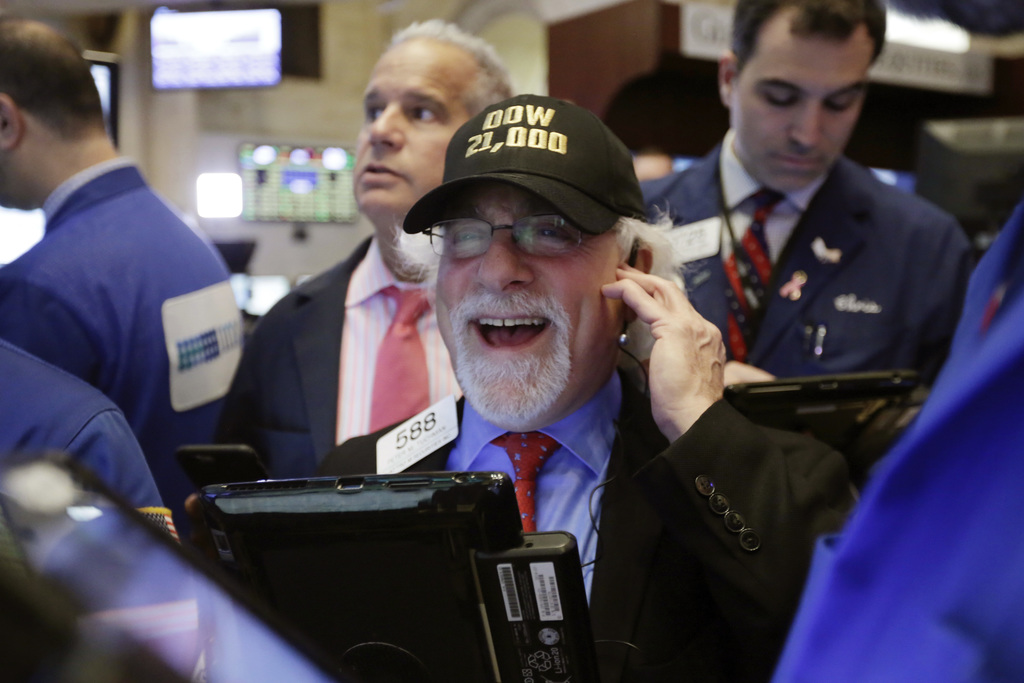 """FILE - In this Wednesday, March 1, 2017, file photo, trader Peter Tuchman wears a """"Dow 21,000"""" hat as he works on the floor of the New ..."""