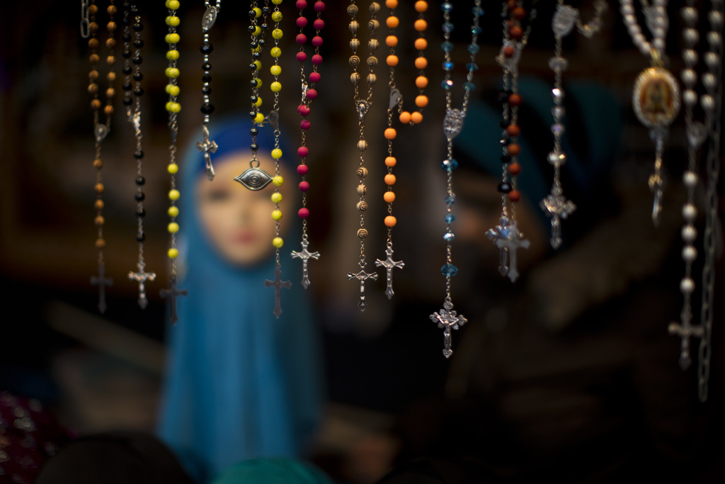 In this Saturday, March 4, 2017 photo, rosary beads are displayed for selling next to a mannequin wearing a headscarf in a market stall...