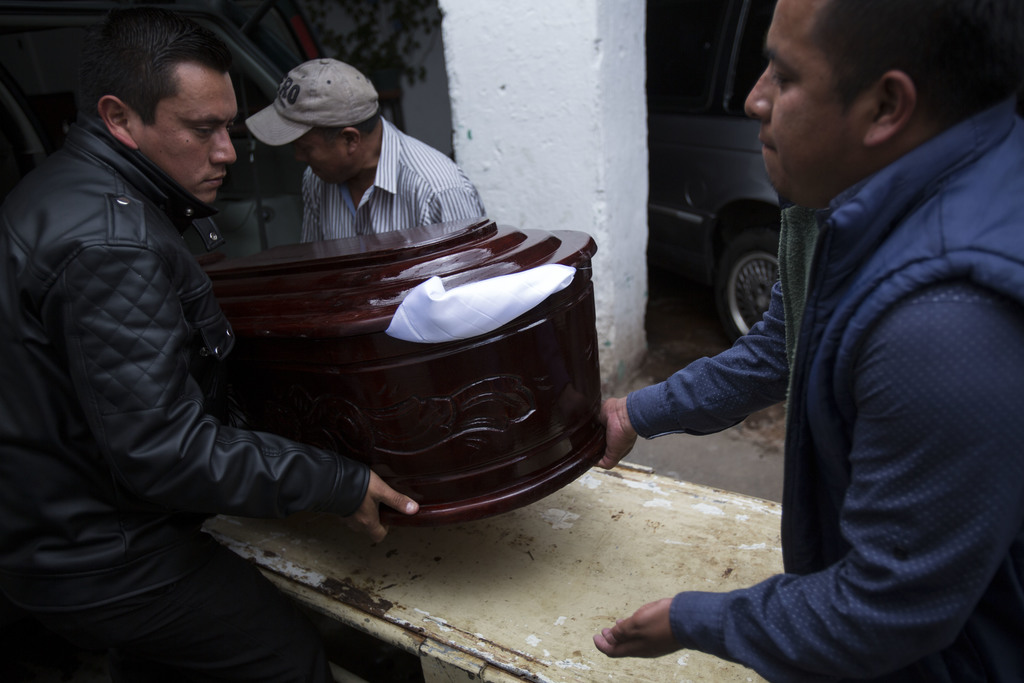 Employees of a funeral home load the coffin of Keila Salguero, a victim of the Virgin of the Assumption Safe Home fire, at the morgue i...