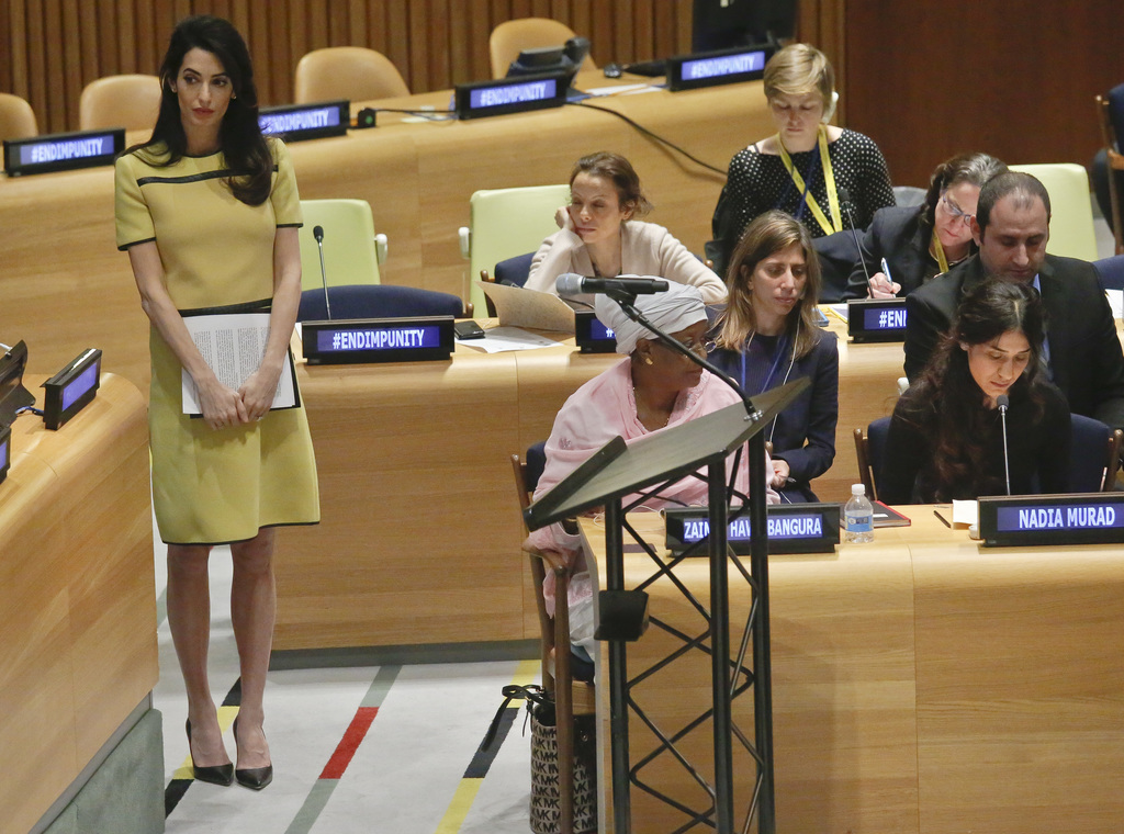 "Human rights lawyer Amal Clooney, left, stands by before addressing a United Nations human rights meeting called ""The Fight against Imp..."