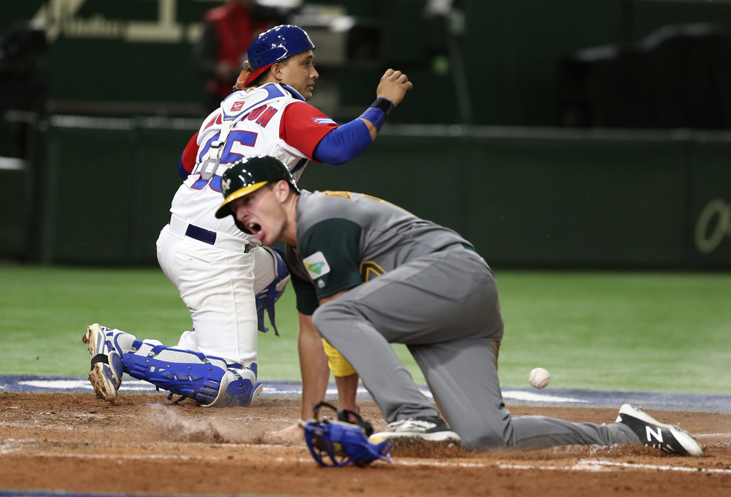 Australia's Mitch Dening, foreground, scores on Logan Wade's single as Cuba's catcher Frank Morejon drops the ball during the fifth inn...