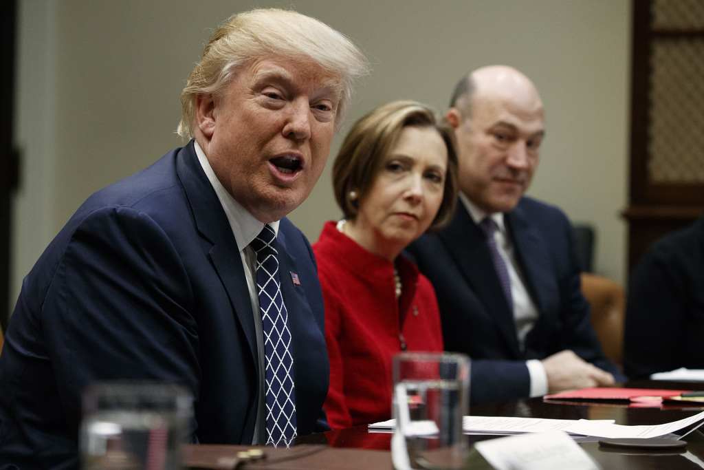 President Donald Trump, accompanied by Cape Cod Five Cents Savings Bank CEO Dorothy Savarese, center, and National Economic Council Dir...
