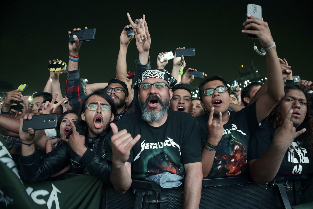 In this Sunday, March 5, 2017 photo, Metallica fans watch the band's performance at a concert in Mexico City. (AP Photo/Marco Ugarte)  ...