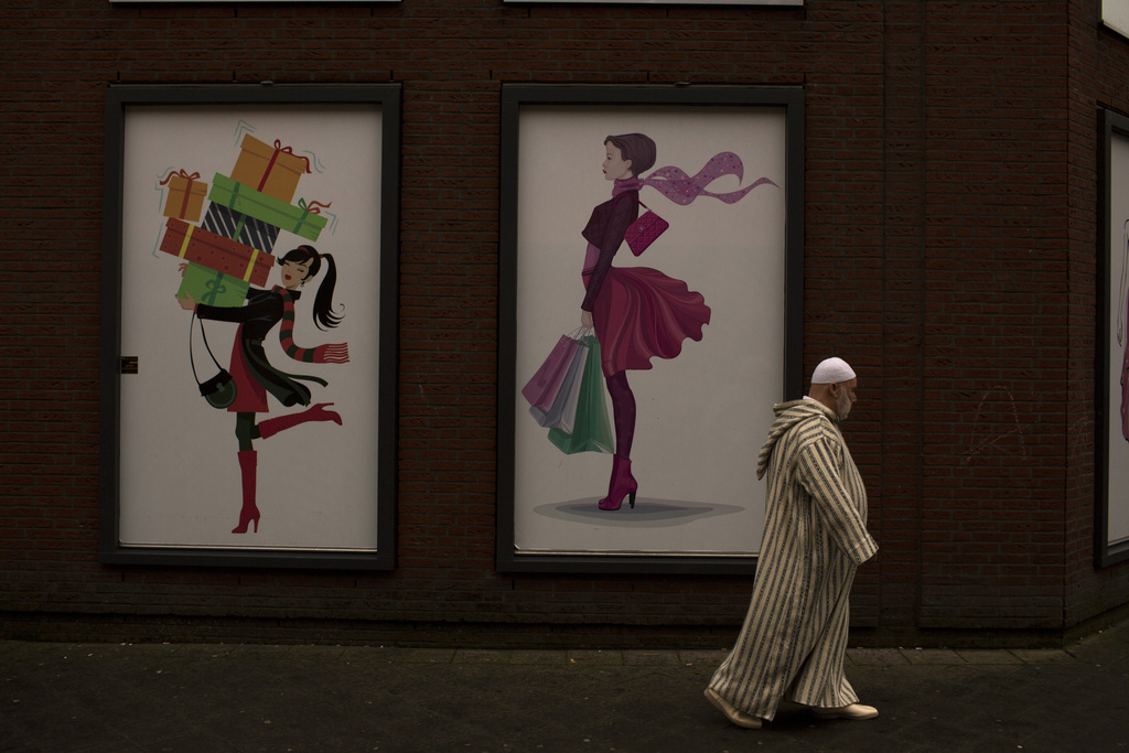 In this Friday, March 3, 2017 photo, a man walks past a clothes shop in the The Hague, The Netherlands. Islam is relatively new in the ...