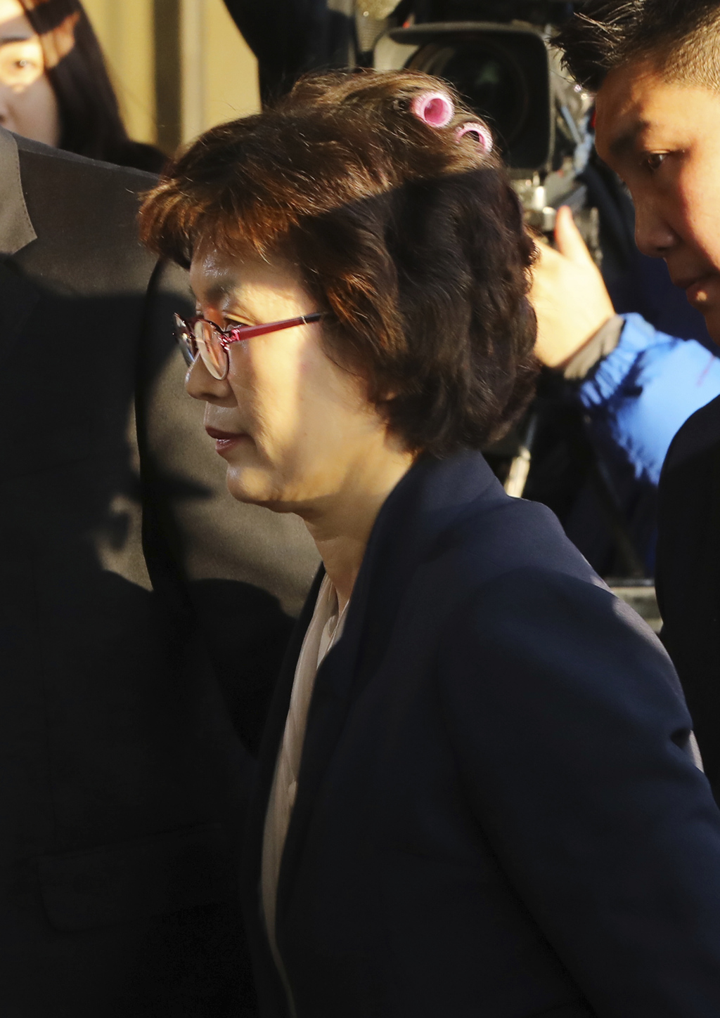 Acting Chief Justice Lee Jung-mi arrives with curlers in her hair at the Constitutional Court in Seoul, South Korea, Friday, March 10, ...